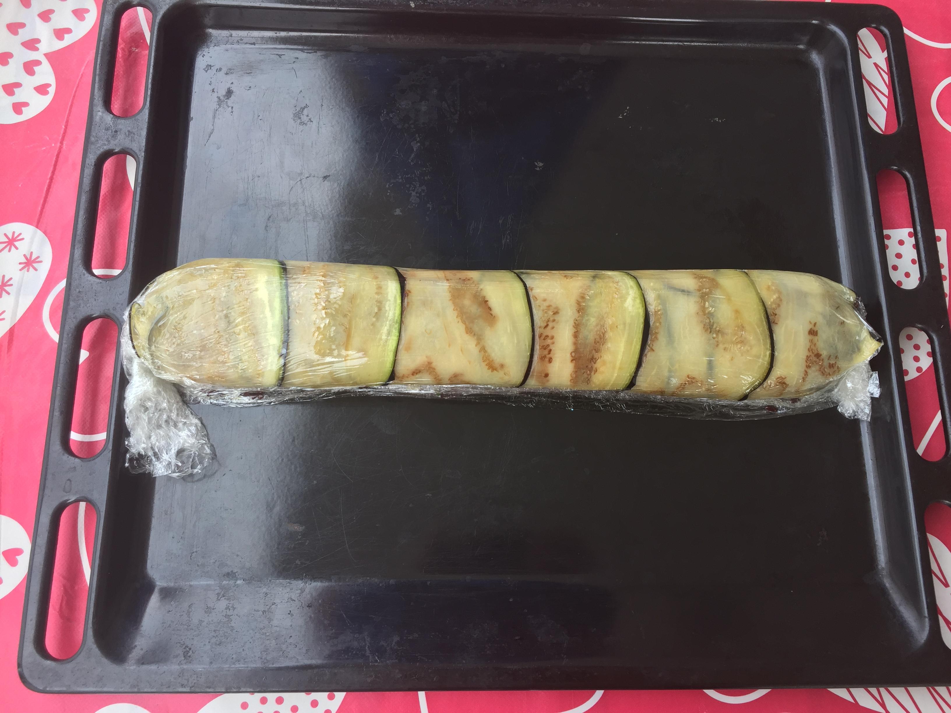 Siamo arrivati alla terza e ultima fase per la preparazione delRolle' di melanzane con riso venere. Per comodità ho utilizzato una placca da forno per lavorare il rotolo. L'ho rivestita con la pellicola trasparente (foto 1). Ho distribuito le fette di melanzane fritte su tutta la superficie (foto 2). A questo punto, condire il riso venere con le melanzane tagliate a dadini (foto 3)