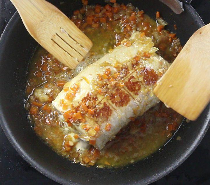 girare l'arrosto di maiale ripieno a metà cottura