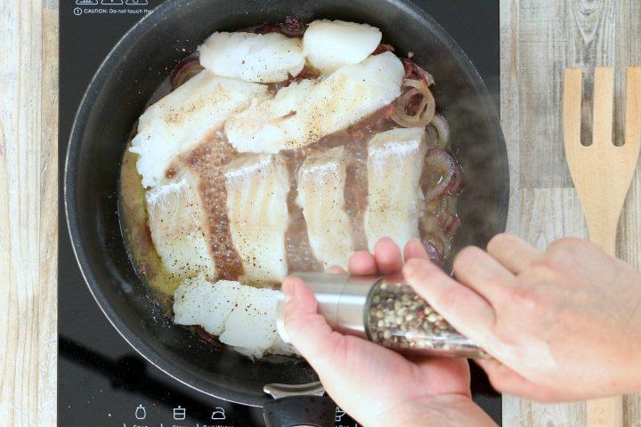 salare e pepare il filetto di merluzzo in cottura