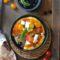 Pizza con pomodorini gialli,rossi, mozzarella di bufala e olive nere
