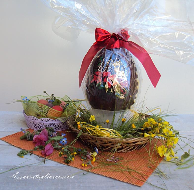 uovo di Pasqua in decorato con glassa colorata, in carta trasparente, su cestino con fiori di prato