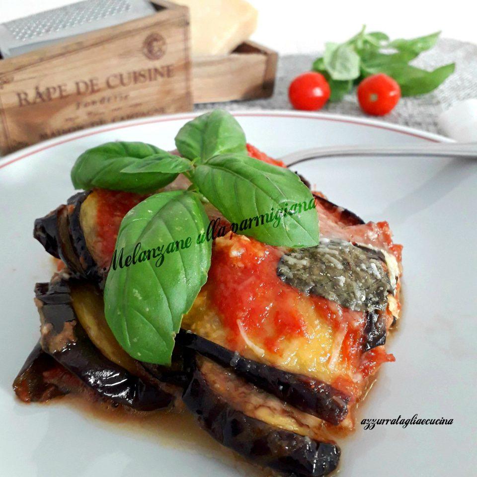 Melanzane alla parmigiana su piatto bianco con sfondo di pomodorini