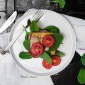 Tempeh alla besciamella di mandorle con spinacino novello e pomodori