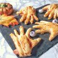 Mani di halloween fatte con pasta sfoglia ripiene di passata di pomodoro salsiccia e formaggio filante