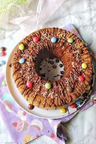 Ciambella di carnevale con glassa al cioccolato fondente e confetti i colorati