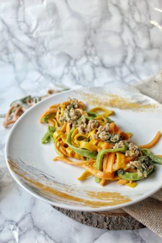 Tagliatelle colorate verdi rosse e arancioni fatte a mano condite con macinato speck e spinaci