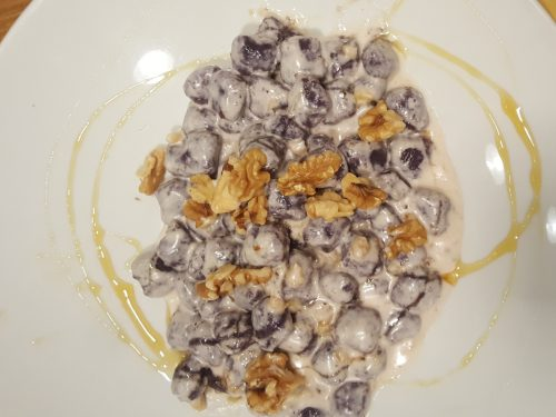 Gnocchi di patate viola al Castelmagno D.O.P. con noci e miele d'acacia.