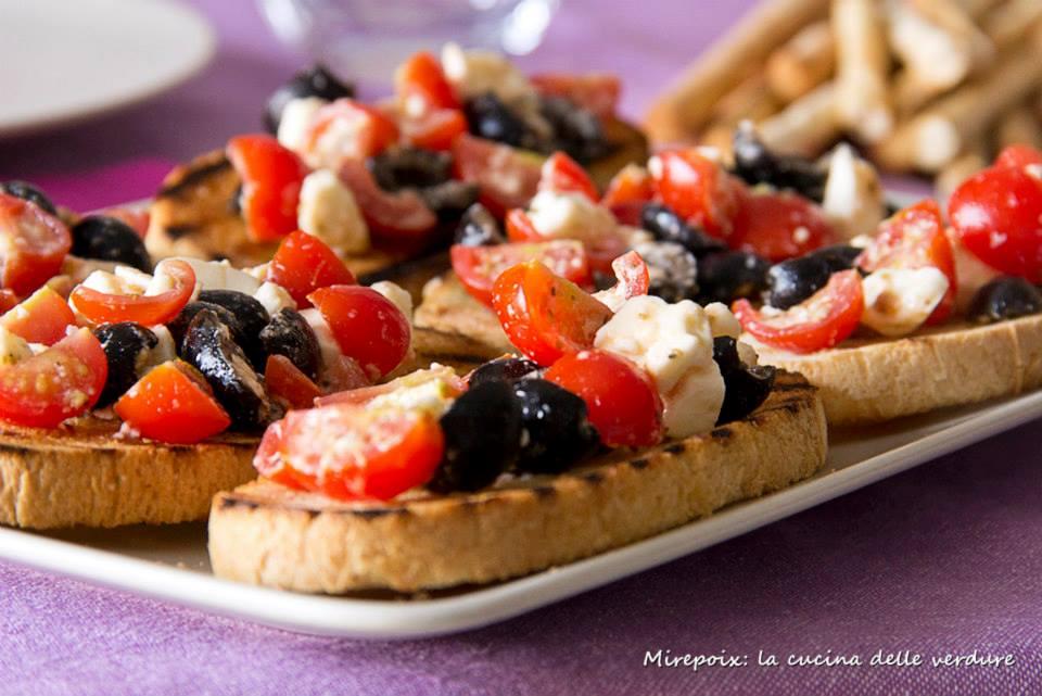 Bruschette con Pachino, feta e olive nere all'origano.