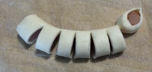 Ora piegate il primo pezzo di würstel vero la vostra destra, fate così con  tutti i pezzi dando una forma circolare.
