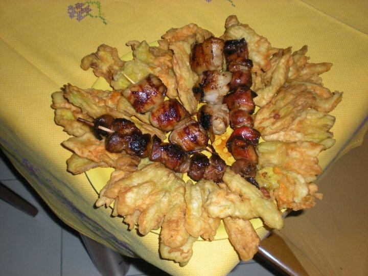 Spiedini di carne arrotolati in pancetta con contorno di fiori di zucchina pastellati