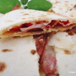 Triangoli di piadina con brie pomodorini e speck – ricetta finger food