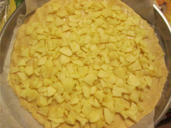 Stendere una parte d'impasto in un tegame con carta forno e distribuirvi le mele .