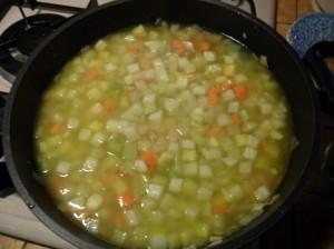una volta soffritte le verdure, aggiungere le patate e coprire con il brodo vegetale