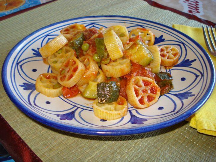 ruote di pasta alle zucchine piselli e crudo croccante