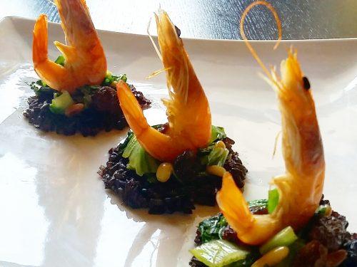 Crostini di riso nero con scarola e mazzancolle