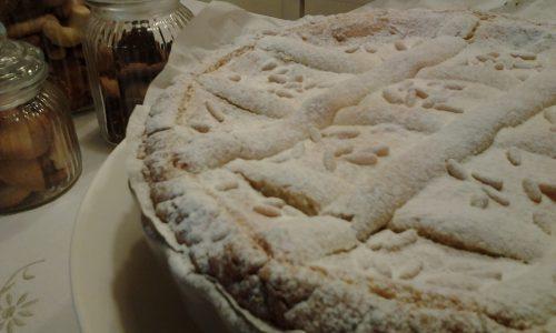 Crostata con crema , ricotta , panna e pinoli aromatizzata alle mandorle