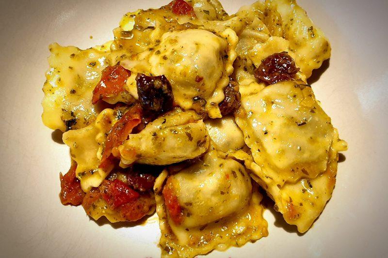Ravioli di borragine con pesto, pomodorini e olive taggiasche