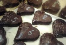 Biscotti al cacao a forma di cuore con copertura di cioccolato al latte fuso e scaglie di cioccolato al latte + decorazione di glassa bianca