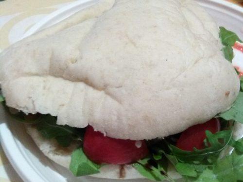 Panino arabo ripieno di rucola, hamburger di carne home-made e pomodorini