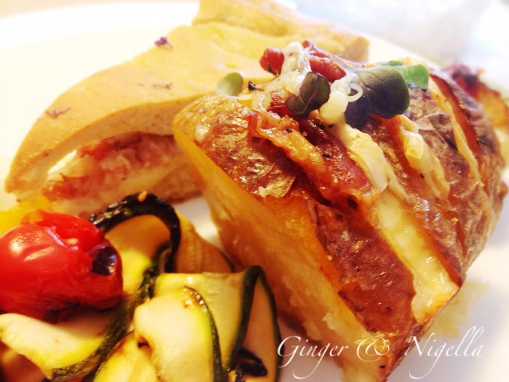 Porzione di patata alla Hasselback per un apericena accompagnato con spiedino di verdure (zucchine, datterini e peperoni) e focaccia soffice farcita con scamorza, pancetta al Barolo e porri Pastorizzati.