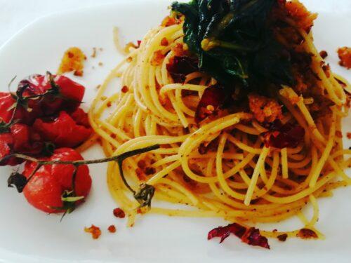 Spaghetti con mollica di pane, peperoni cruschi, ramoracce e pomodorini al grappolo