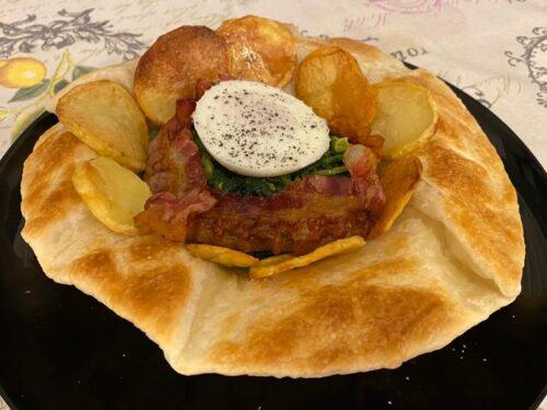 Uova in camicia in un cestino di pasta sfoglia con cime di rapa, bacon e patate al forno