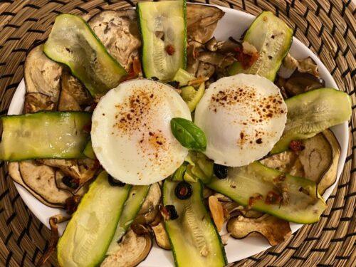 Uova in camicia su verdure al forno condite con pomodorini secchi, olive e liquirizia