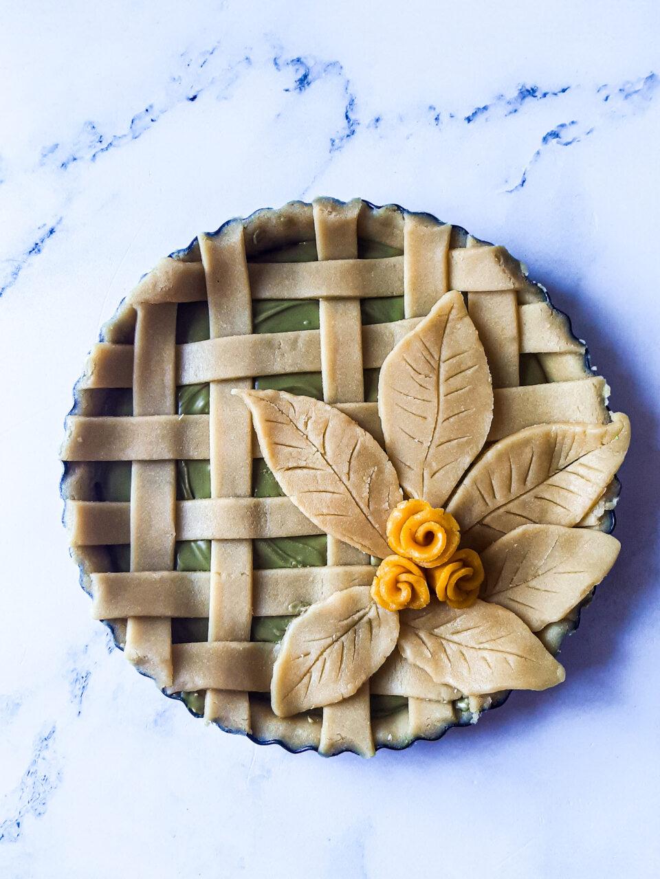 crostata con crema al pistacchio, foglie e fiori