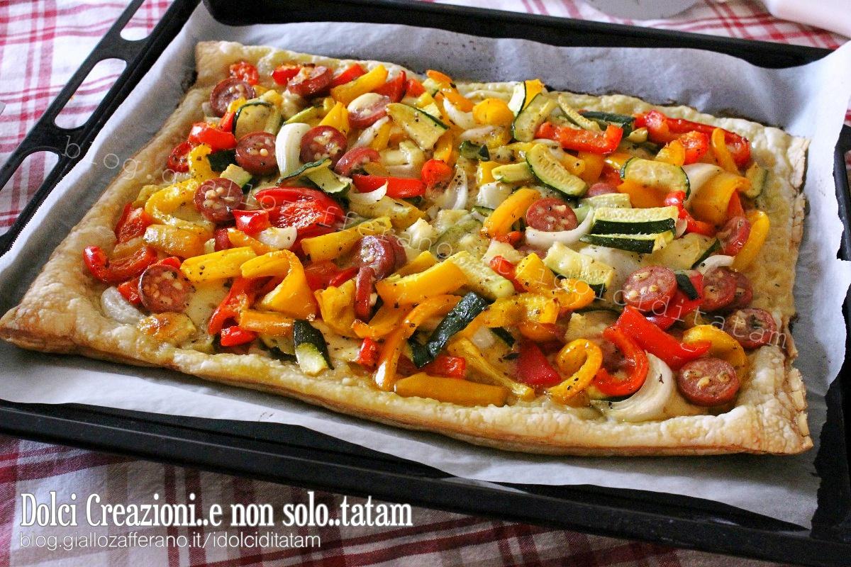 Per preparare la Pizza di pasta sfoglia alle verdure incominciare con il  lavare le verdure quindi ridurre a listarelle i peperoni, a filetti la  zucchina e a