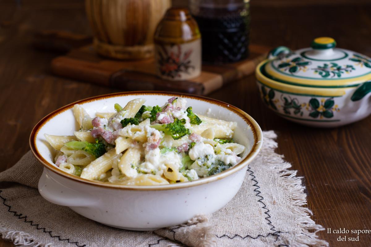 Pulite e affettate una cipolla piccola, rosolatela in un buon giro d'olio d'oliva, unite la pancetta e lasciate cuocia qualche minuto.  Aggiungete le cimette dei broccoli, salate appena e rosolate, aggiungete un po' d'acqua e portate a cottura desiderata, ma meglio lasciarli un po' al dente.  In una ciotola mischiate i broccoli alla ricotta, aggiungete i due formaggi e mescolate, aggiustate di sale.