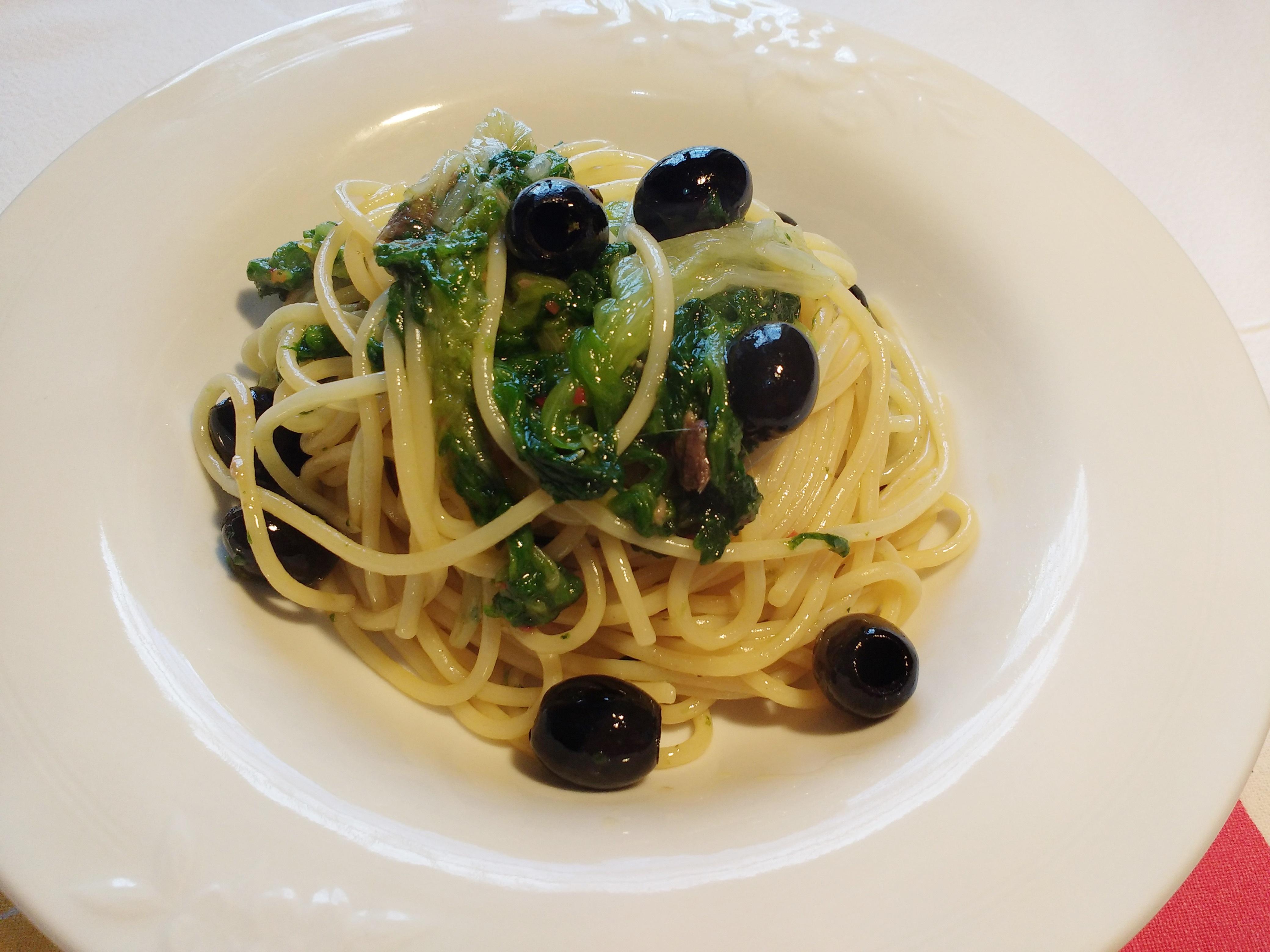 spaghetti con scarola , alici e olive nere