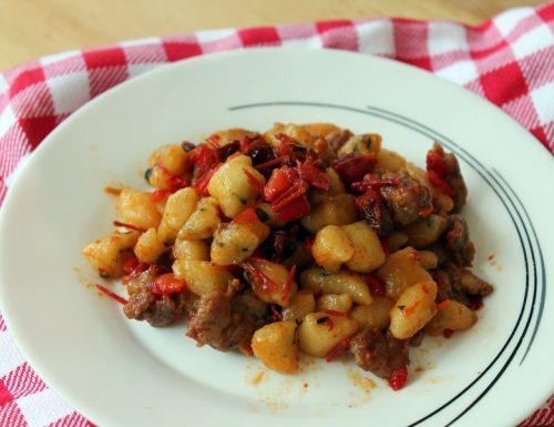 Gnocchi al basilico con salsiccia peperoni e pomodori secchi