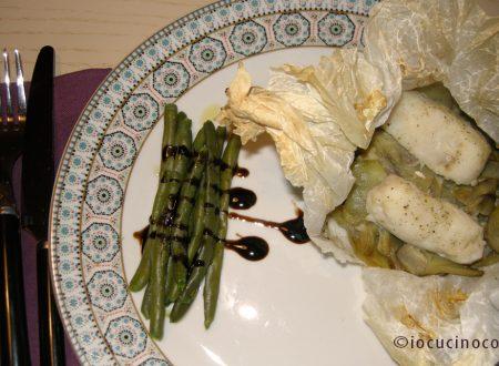 Nasello al cartoccio su letto di patate e carciofi | Ricetta secondo di pesce