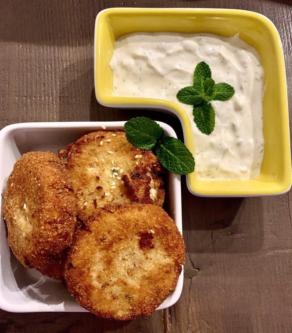 deliziose polpette di baccalà adagiate su una terrina bianca con foglioline di menta, accompagnate da una squisita crema all'aneto con yogurt greco