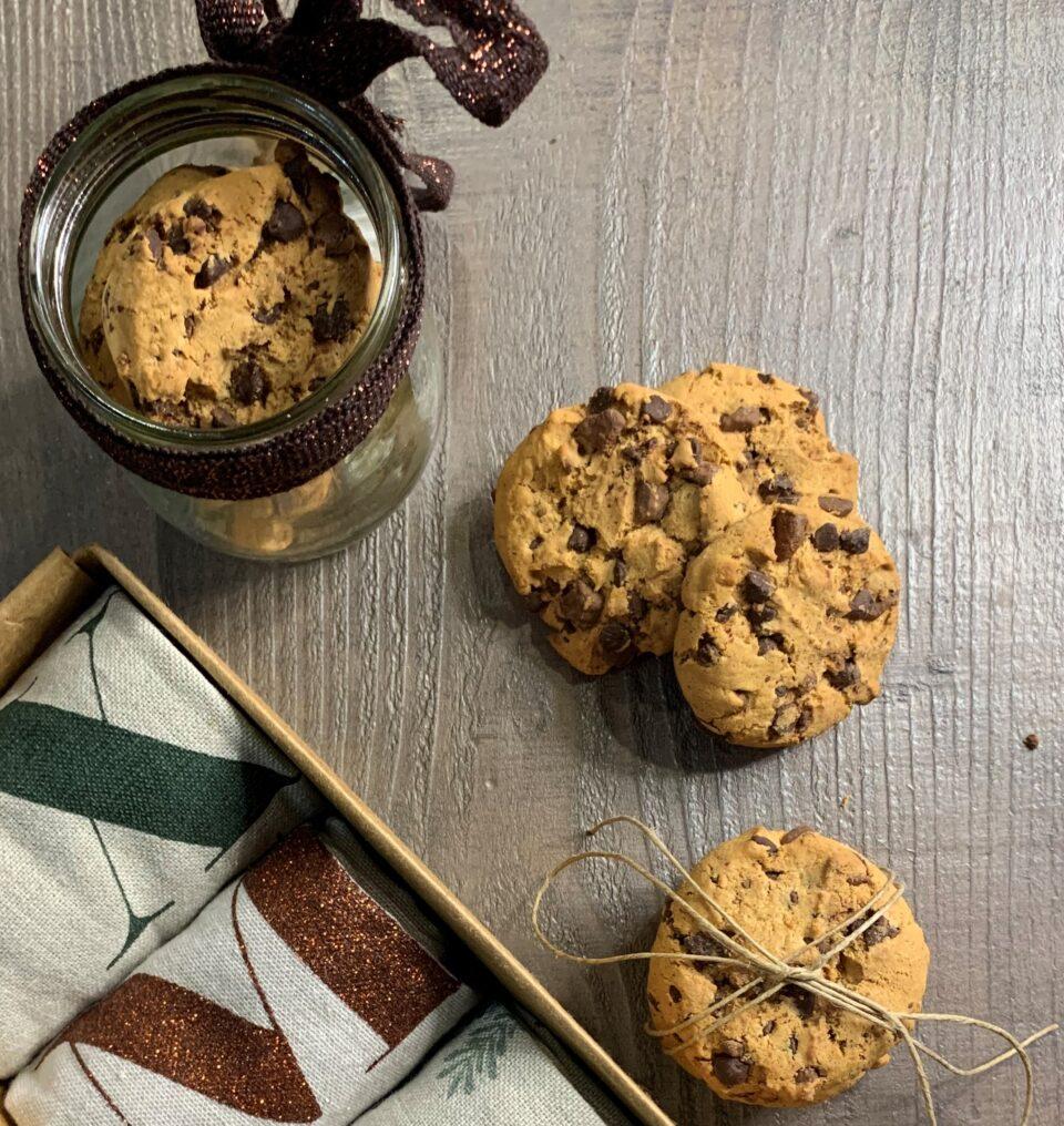 cookies con gocce di cioccolato adagiati su sdi un tavolo di legno a formare una torretta, altri in una barattolo con un nastrino brillante e altri ancora legati con uno spago