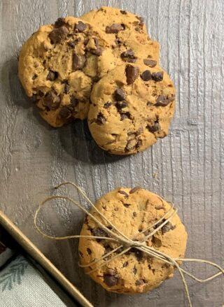 biscotti cookies con gocce di cioccolato fondente adagiati su tavolo di legno, impilati l'un l'altro per formare una torre e tenuti insieme dallo spago