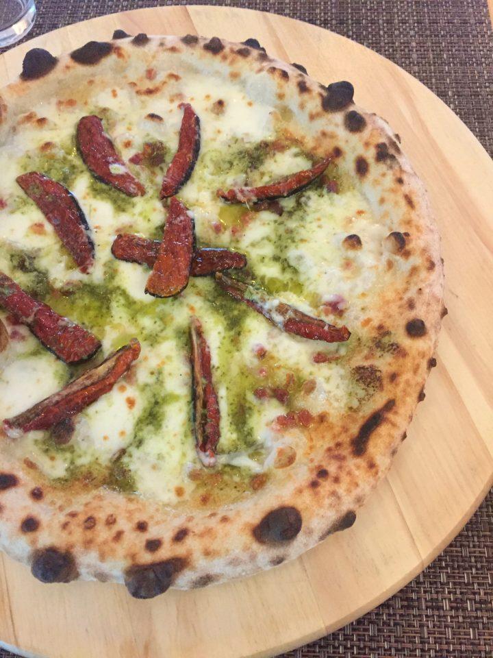 pizza con pomodori secchi, pesto e pancetta croccante