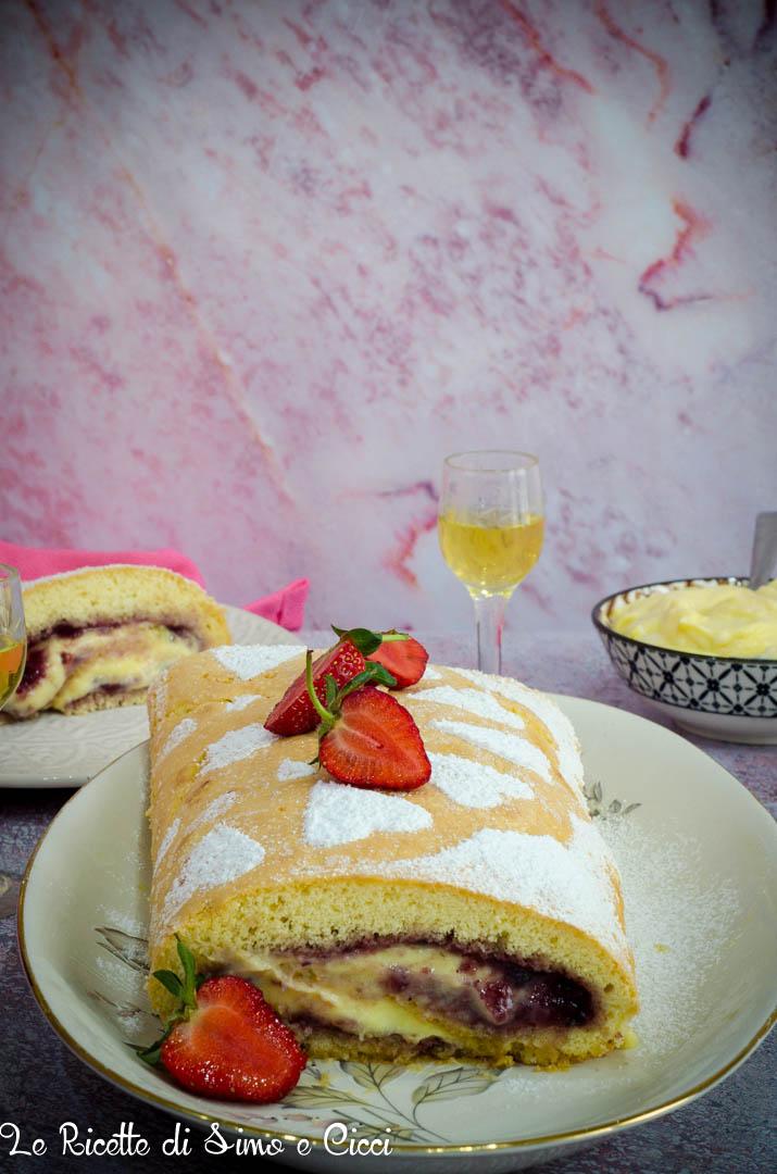 Rotolo con crema al limone e frutti di bosco su vassoio con fragole e zucchero a velo