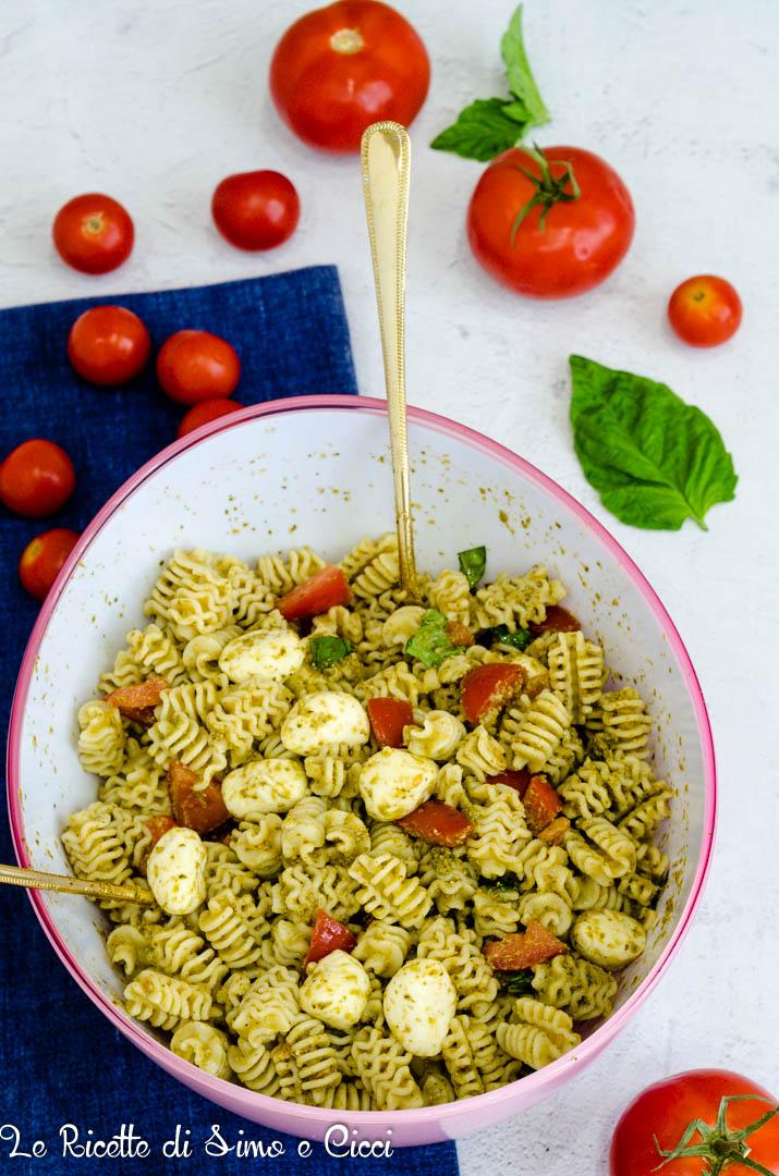 Pasta Fredda con Pesto Pomodori e Mozzarella  su un panno blu con pomodori e foglie di basilico
