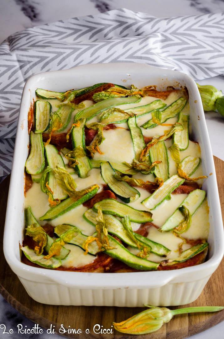 Torta di pane zucchine e mozzarella in pirofila con panno bianco e grigio e fiori di zucca