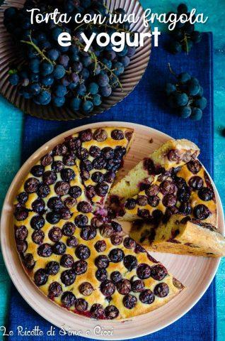 Fette di torta su un piatto rosa e uva fragola