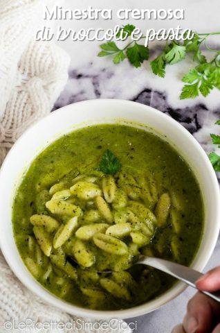 Ciotola con minestra verde e pasta e mano con cucchiaio