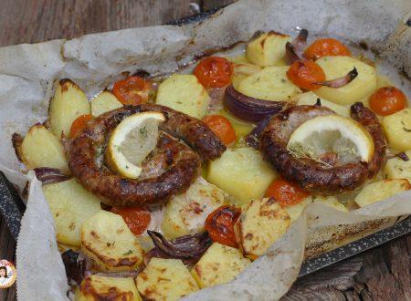 Salsiccia al forno con patate, pomodorini e cipolla