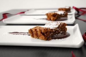 Torta umida alla frutta secca su crema di cioccolato fondente