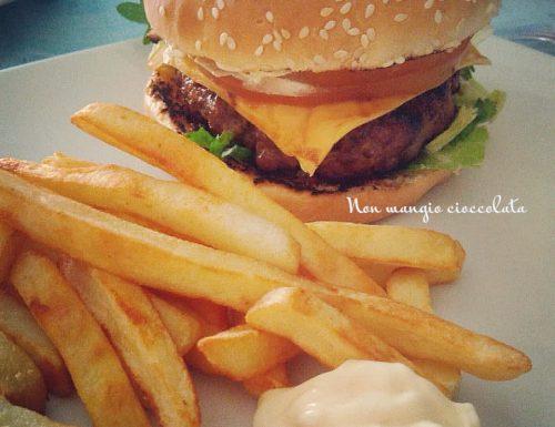 Panino al sesamo con hamburger di carne e contorno di patate