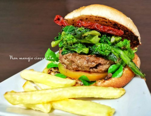 Panino al sesamo con hamburger di carne, cime di rapa stufate e pomodori secchi