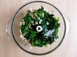 Tritare le ortiche, con l'aglio, i pinoli ed il sale