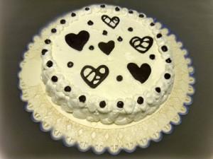 torta decorata con panna con cuori di cioccolato fondente