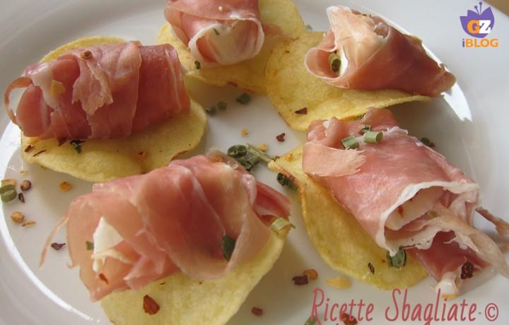 Involtini prosciutto e mozzarella piccanti su patatine, idea buffet