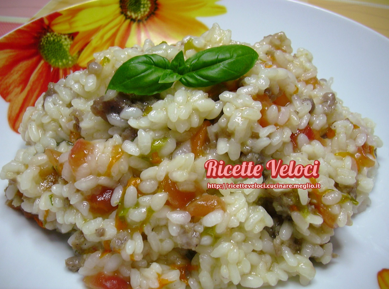 Risotto con fiori di zucca salsiccia basilico e pomodoro